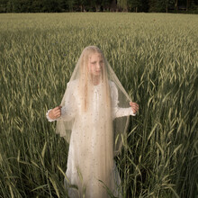 Blonde Girl In A White Vintage Dress Standing In A Wheat Field With A Thin Veil