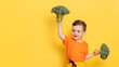 A studio shot of a boy holding a fresh broccoli. The concept of healthy baby food. Space for your text