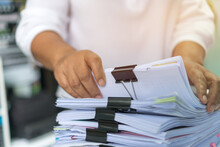 Office Workers Arranging Stacks Of Lot Documents Report Papers With Clips Waiting Be Managed On Desk In Busy Office. Concept Of Workload In Business Finacial Paperwork Information Planing