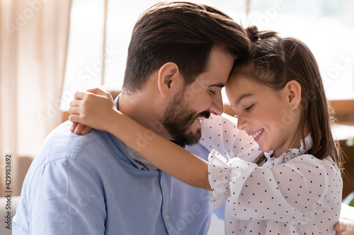 Fototapeta Smiling young Caucasian father and teen daughter hug cuddle show love and care in family relationship. Happy dad parent and teenage small girl child embrace enjoy closeness. Bonding concept. obraz