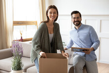 Portrait Of Happy Caucasian Young Couple Renters Open Unbox Packages Moving To New House Or Apartment. Smiling Man And Woman Tenants Settle In Own Home Relocate Together. Relocation, Rent Concept.