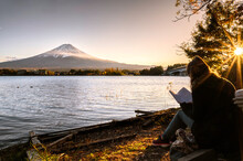 European Tourists Spend Their Free Time To Sit And Read On The Lake Kawaguchiko Japan.