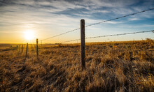 Sunrise Behind A Wooden Barbed Wire Fence Over Natural Prairie Grasslands In Alberta Canada.