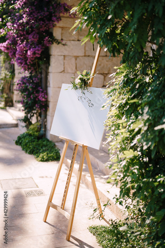 Photo Blank wooden easel on the background of the wall and flowering bushes
