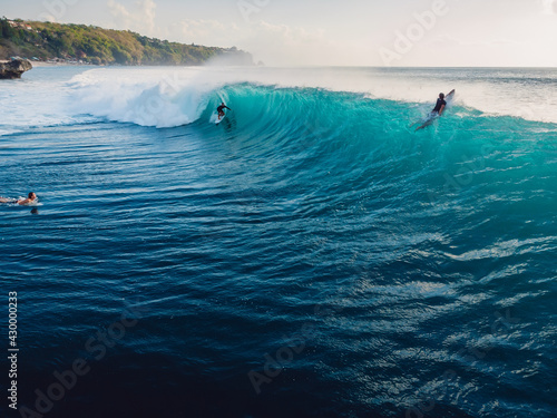 Aerial view with surfing on ideal wave. Blue perfect waves and surfers in ocean