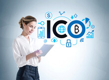 Businesswoman With Tablet In Hands And Cryptocurrency Icon On Blue Wall