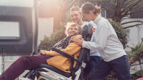 Fototapeta premium Two helpers picking up disabled senior woman for transport
