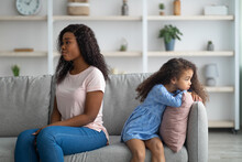 Offended Black Woman And Her Daughter Sitting Back To Back On Sofa, Not Speaking To Each Other After Fight At Home