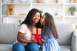 Leinwandbild Motiv Mother's Day celebration. Lovely little black girl giving mom wrapped holiday gift and kissing her on cheek at home