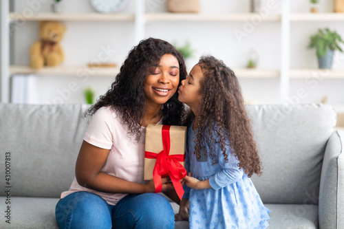 Mother's Day celebration. Lovely little black girl giving mom wrapped holiday gift and kissing her on cheek at home