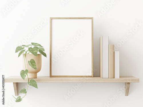 Obraz na plátně Small vertical wooden frame mockup in scandi style interior with trailing green plant in pot, pile of books and shelf on empty neutral white wall background