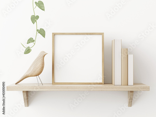 Fototapeta Small square wooden frame mockup in scandi style interior with trailing green plant, bird, pile of books and shelf on empty neutral white wall background. 3d rendering, illustration obraz