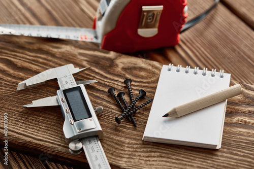Fototapeta Measuring tape, caliper and notebook, macro view obraz