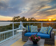 Gorgeous Spring Sunset Glows Behind A Cute Porch Couch And Table Set With Flowers.