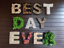 3D Shaped Letters On Wall. Craft Letters Made Of Various Textures Such As Woods, Rope, Fabric, Twine, Leaves, Flowers. Wishing Quote - Best Day Ever. Interior Decoration