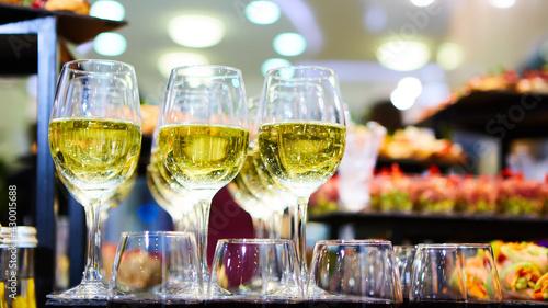 Obraz na plátně Glasses of white wine are on the table, ready to serve.