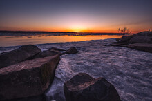 A Beautiful Sunset Over A Large River With Floating Ice And Rocks On The Shore. Spring Season.