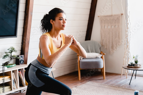 Photographie Young fit afro woman in sporty clothes doing fitness exercises at home