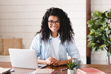 Successful Young Afro Businesswoman Working At Her Office Desk. Front View Of Smiling African American Female Freelancer Working At Home