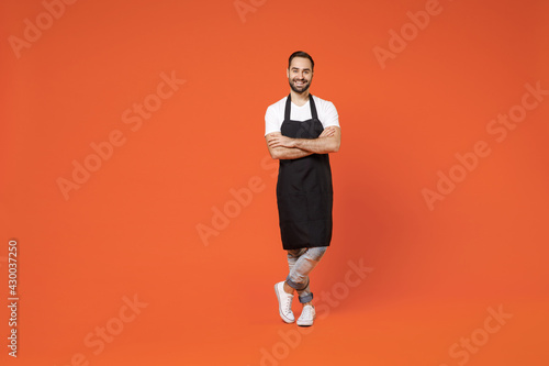 Fotografia, Obraz Full length young man barista bartender barman employee in black apron white tshirt work in coffee shop hold hands crossed folded isolated on orange background studio