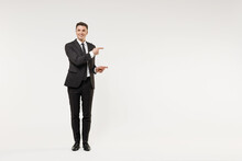 Full Length Young Successful Employee Business Corporate Lawyer Man In Classic Formal Black Grey Suit Shirt Tie Work In Office Point Finger Aside On Workspace Area Isolated On White Background Studio.