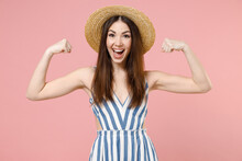 Young Woman In Summer Clothes Striped Dress Straw Hat Showing Biceps Muscles On Hand Demonstrating Strength Power Isolated On Pastel Pink Color Background Studio Portrait. People Lifestyle Concept