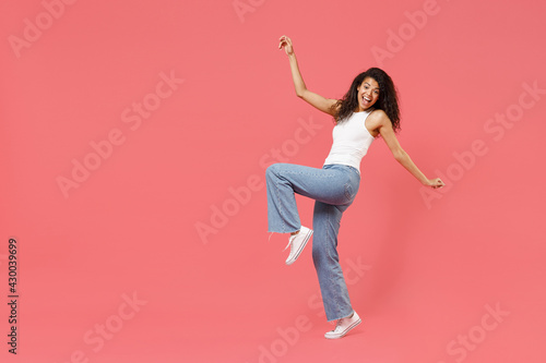 Full length young smiling fun friendly positive african american woman 20s wear casual white tank shirt leaning back standing on toes dancing with outstretched hands isolated on pink color background - fototapety na wymiar
