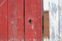 A Closeup Of A Bright Red Vintage Metal Keyholder In A Textured Red Wooden Door. The Exterior Of The Old Woodshed Has Worn And Wear Patterns With Some Scuff Marks.The Door Is On A White Wood Building.