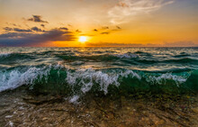 A Wave Is Crashing To The Seashore As The Sun Sets In In The Colorful Sunset Sky