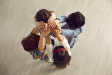 View From Above Of Team Of Children. Group Of Four Kids Standing Close In Circle Raising And Joining Hands Feeling United And Empowered. Communication, Bonding, Help, Community Improvement Concept