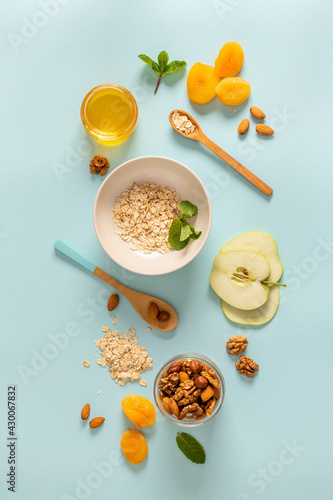 Fototapeta Ingredients for making breakfast with granola and fruits on blue background top view, flat lay. Cooking quick healthy breakfast concept obraz