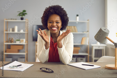 Happily smiling satisfied african american woman worker sitting at table in office looking at camera holding palms up headshot portrait. Funny conversation or successful interview online. Webcam view - fototapety na wymiar