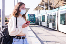Portrait Of Attractive Young Female In Face Mask With Phone Standing On Station, Waiting For Arriving Tram