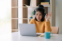 Happy Young Asian Ethnicity Female Manager Wearing Wireless Headphones, Looking At Laptop Screen, Holding Pleasant Conversation With Partners Clients Online, Working Remotely At Workplace.
