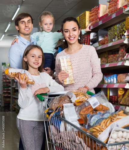 Obraz na plátně Ordinary customers with small children purchasing shortcakes in hypermarket and