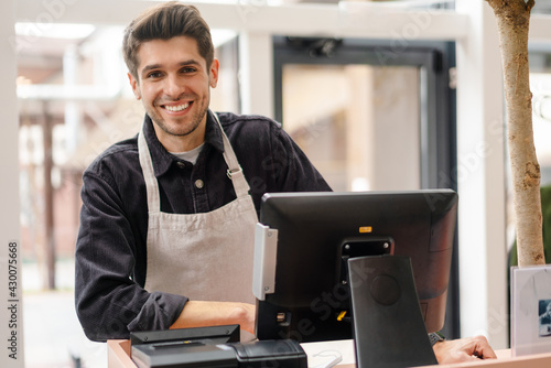 Fotografiet Smiling young man in apron standing at the cash register