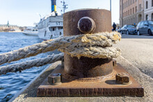 Old Mooring Rope Around The Rusted Iron Bollard