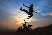 Beautiful Landscape Shadows Of An Old Motorbike On The Top Of The Mountain With Young Man Jumping Kung Fu Pose, The Beautiful Sky