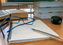 Glasses And A Pen On A Blank Sheet Of Notebook. Books, A Monitor, And Other Items For Work Are On The Table. The Concept Of Education, E-learning, Scientific Work.