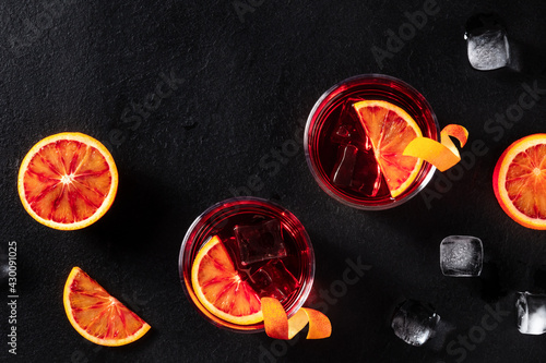 Negroni cocktails with blood oranges and ice, shot from above - fototapety na wymiar