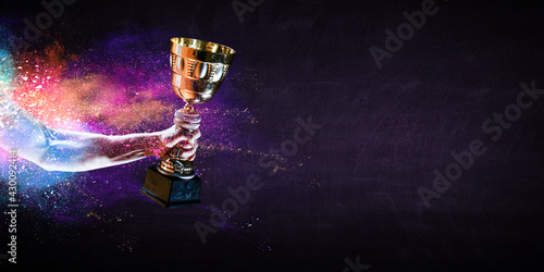 Fototapeta premium Hand holding up a gold trophy cup against dark background