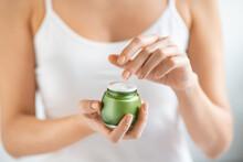 Woman Applying Moisturizer From Jar
