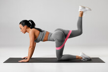 Athletic Girl Doing Kickback Exercise For Glutes With Resistance Band. Fitness Woman Working Out Donkey Kicks.