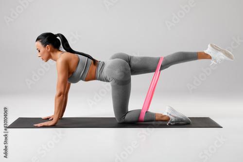 Valokuvatapetti Athletic girl doing kickback exercise for glutes with resistance band