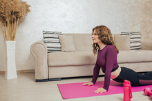 Young Slim Woman In Cobra Pose Practicing Yoga At Home.