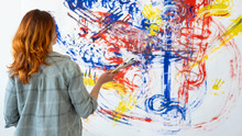 Painting Art. Interior Decor. Creative Design. Back View Portrait Of Inspired Redhead Woman Painter With Brushes Looking At Blur Colorful Blue Red Yellow Abstract Artwork On White Wall Background.