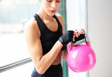 Close Up Of Young Beautiful Woman Doing Crossfit In A Gym With A Pink Kettlebell, White Background Horizontal View