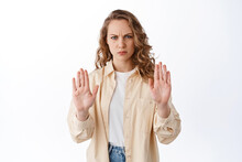 Displeased Blond Woman Frowning, Showing Stop Block Gesture, Refusing Offer, Say No And Reject Something Bad, Standing Over White Background