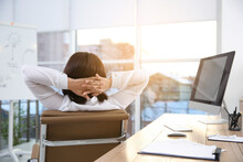 Woman Relaxing In Office Chair At Workplace, Back View