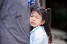 Adorable Asian Girl Is Crying With Tears On Her Cheeks. Child Rested On Her Mother's Belly. Children Is In Pain From Heartache. A 4 Years Old Wear Light Blue Shirts.